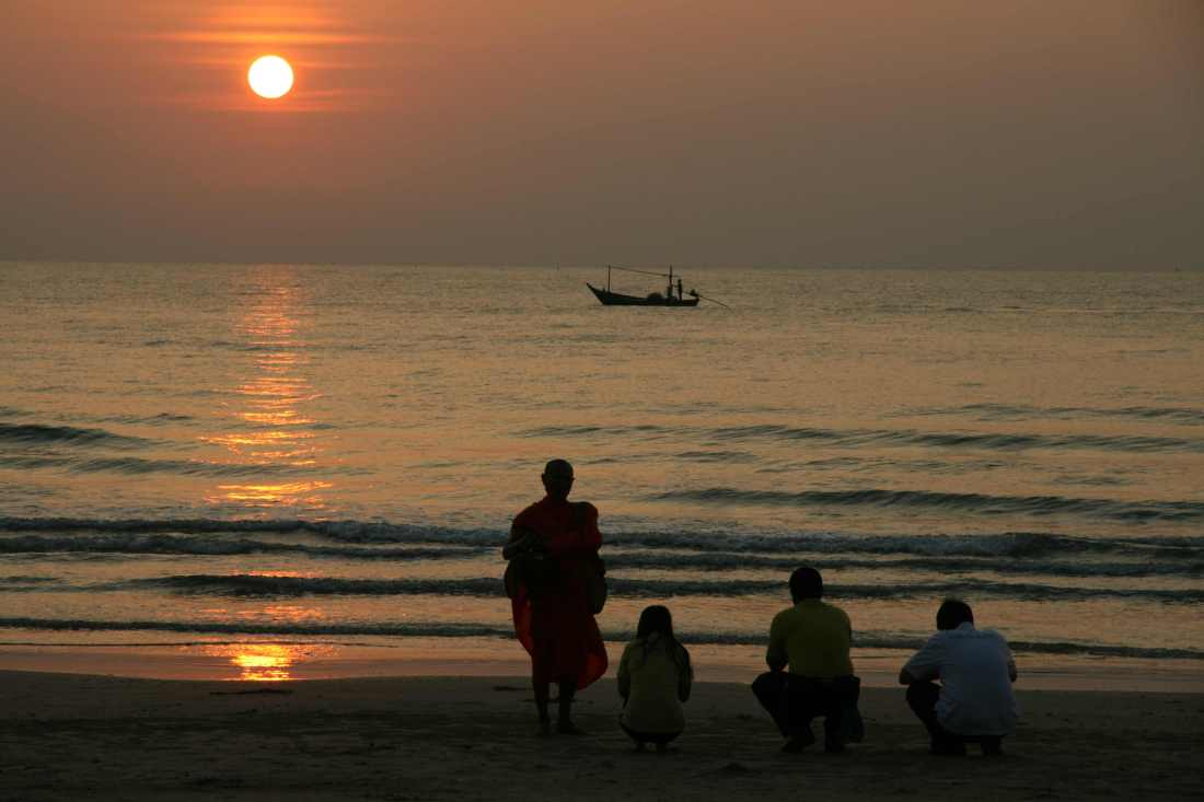 A Buddhist monks blesses tourists on a beach in Thailand