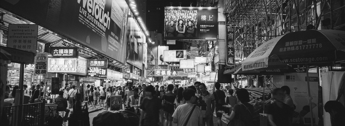 Pedestrians on street lined with shops in Hong Kong